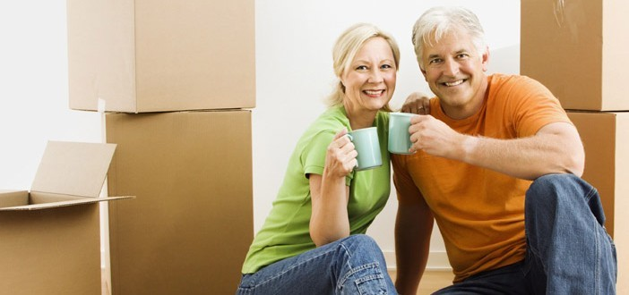 Smiling senior couple sitting in front of moving boxes with coffee mugs in hand