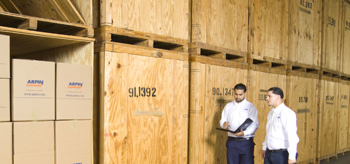 Two warehouse workers in front of storage units