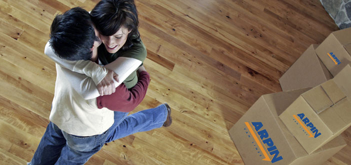 Happy couple hugging in front of moving boxes