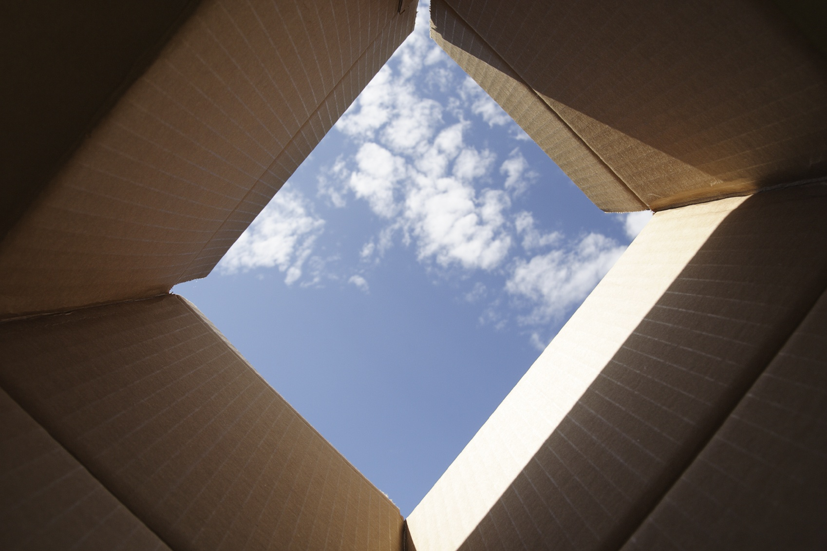 Looking up through a moving box to a blue sky