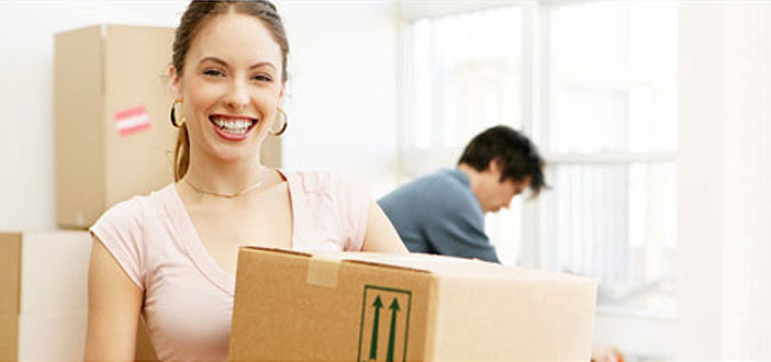 Smiling woman carrying a moving box